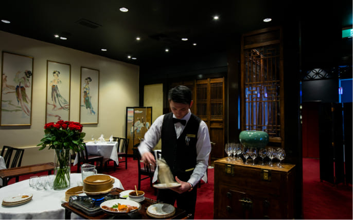 waiter in front of yum cha cart
