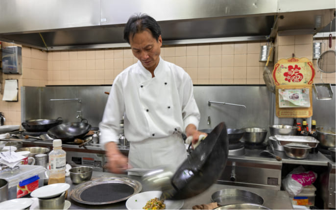 chef cooking with wok