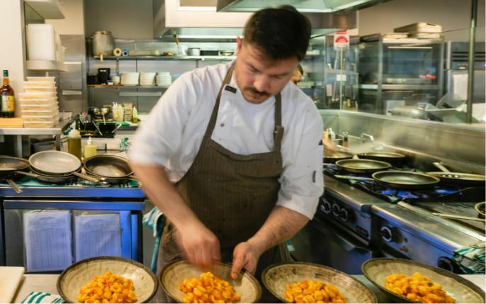 chef dishing up gnocchi bowls