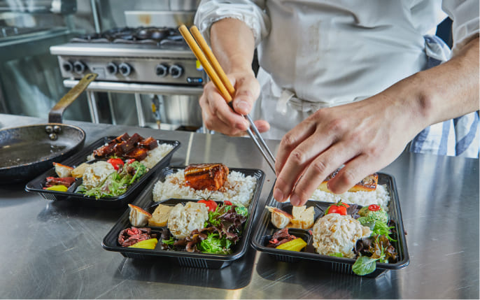 chef prepping bento boxes